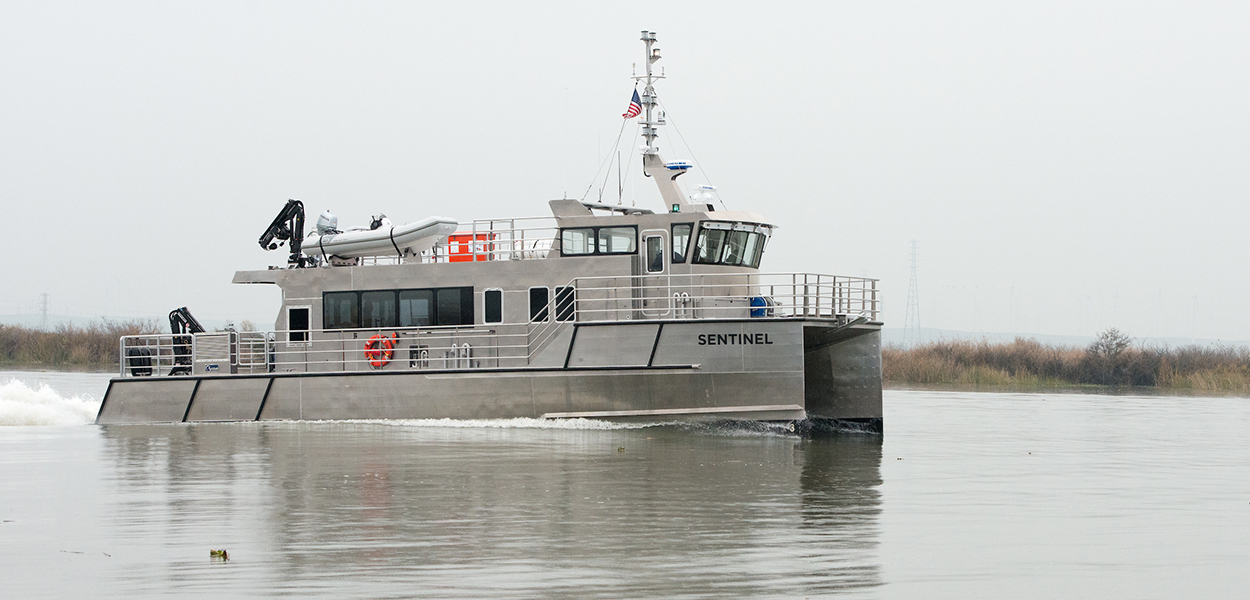 A Delta Interagency Ecological Program research vessel, the Sentinel, sails on the San Joaquin River near the Antioch bridge.